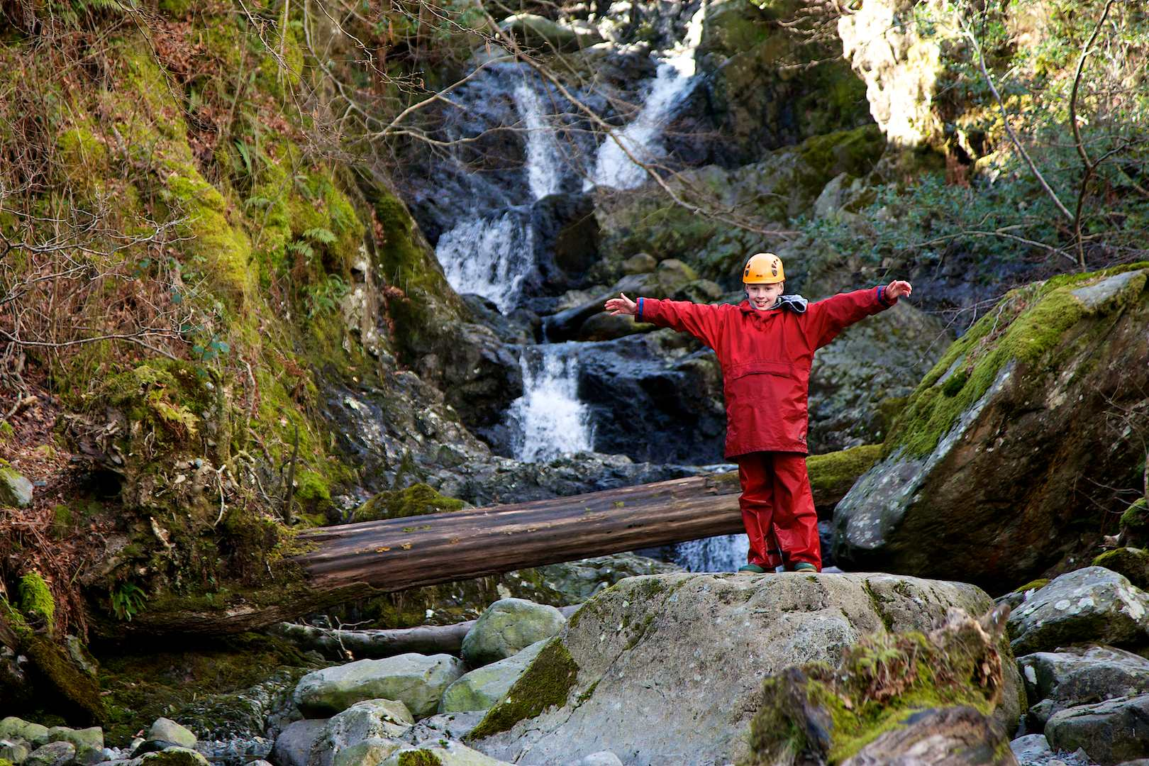 Pupil with arms outstretched by a big waterfall