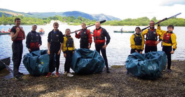 Happy family, wearing wetsuits, standing with homemade corracles, by Derwent Water