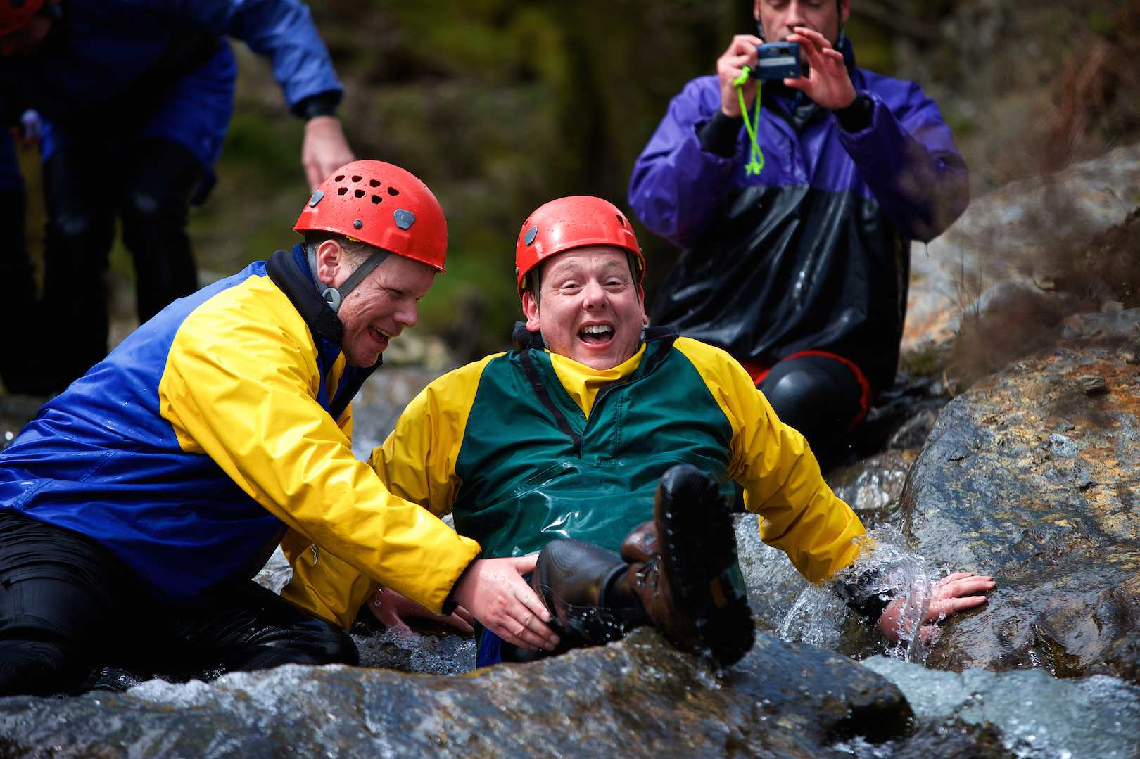 Adults enjoying team working on a wet gorge walk session