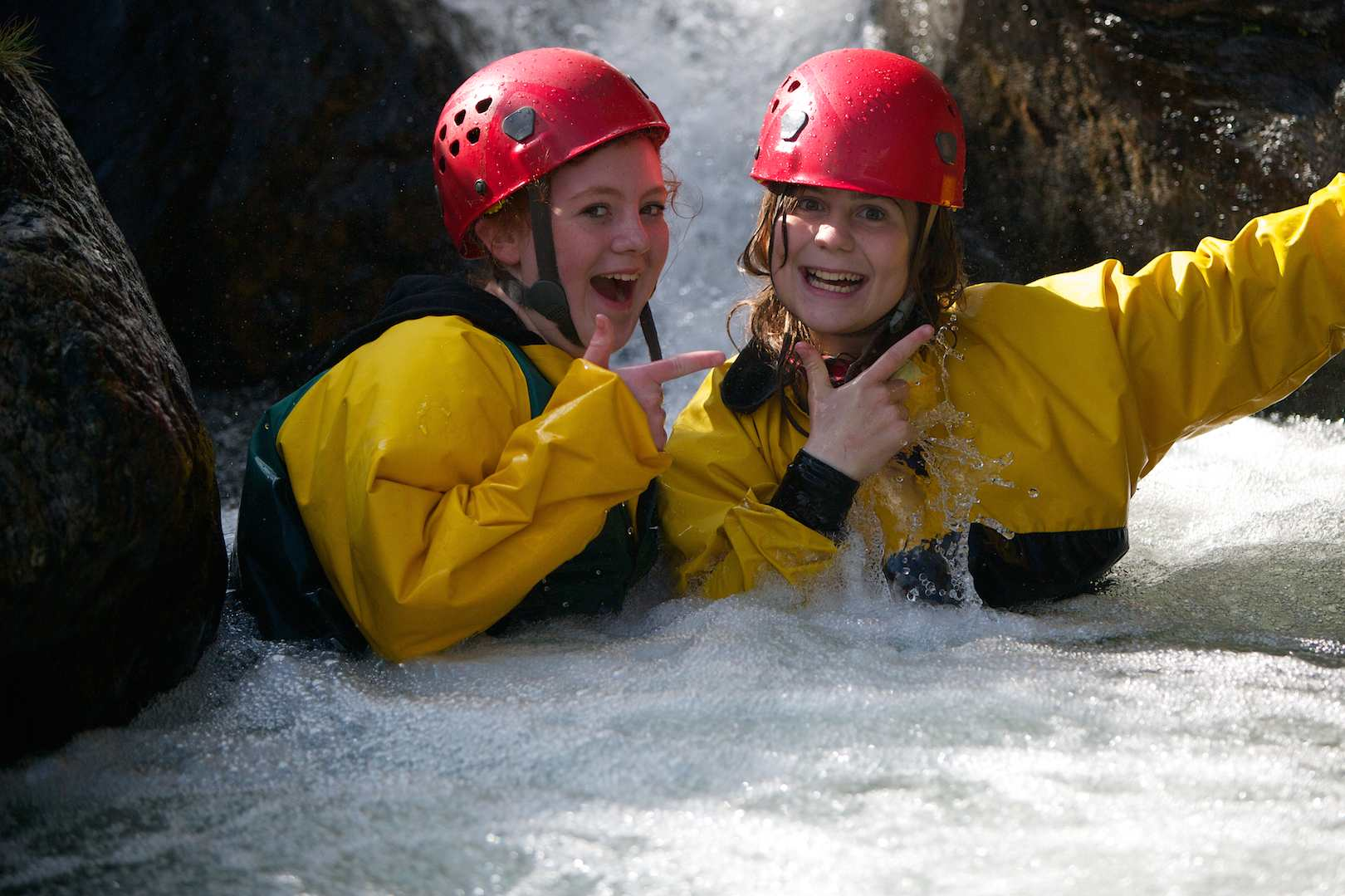 Happy teenage pupils posing in a waterfall in the gorge
