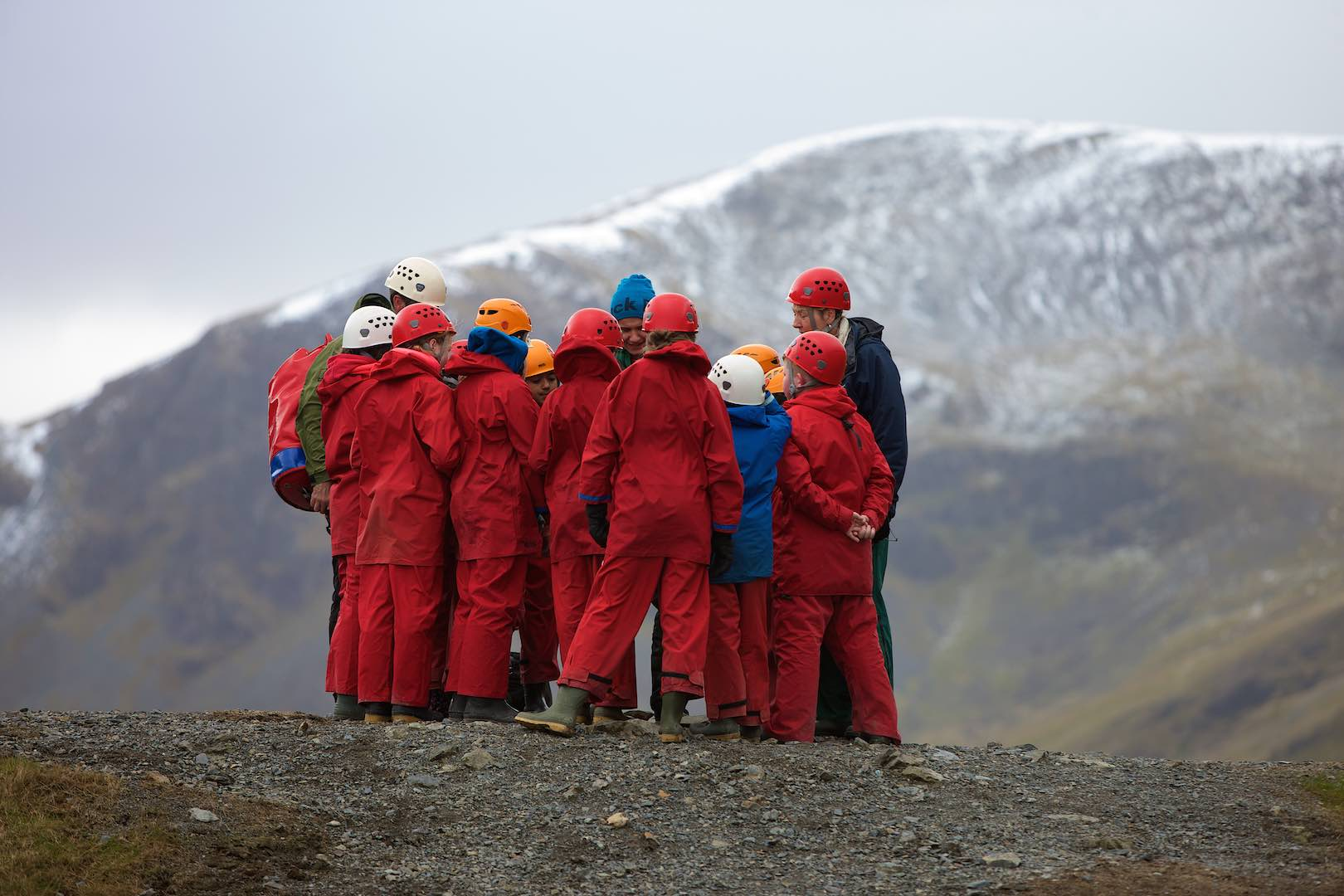 Primary pupils huddled together among the mountains learning about geology