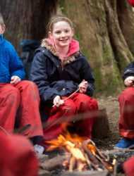 Pupils review learning around a camp fire