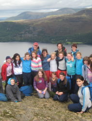 Year six class grouped together on the Summit of Catbells