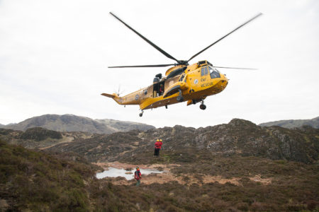 An RAF Seaking winching Mountain Rescue Team members from a mountain side