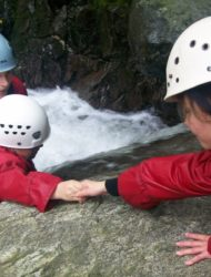 Teamwork in action. Two primary school pupils helping each other in the gorge