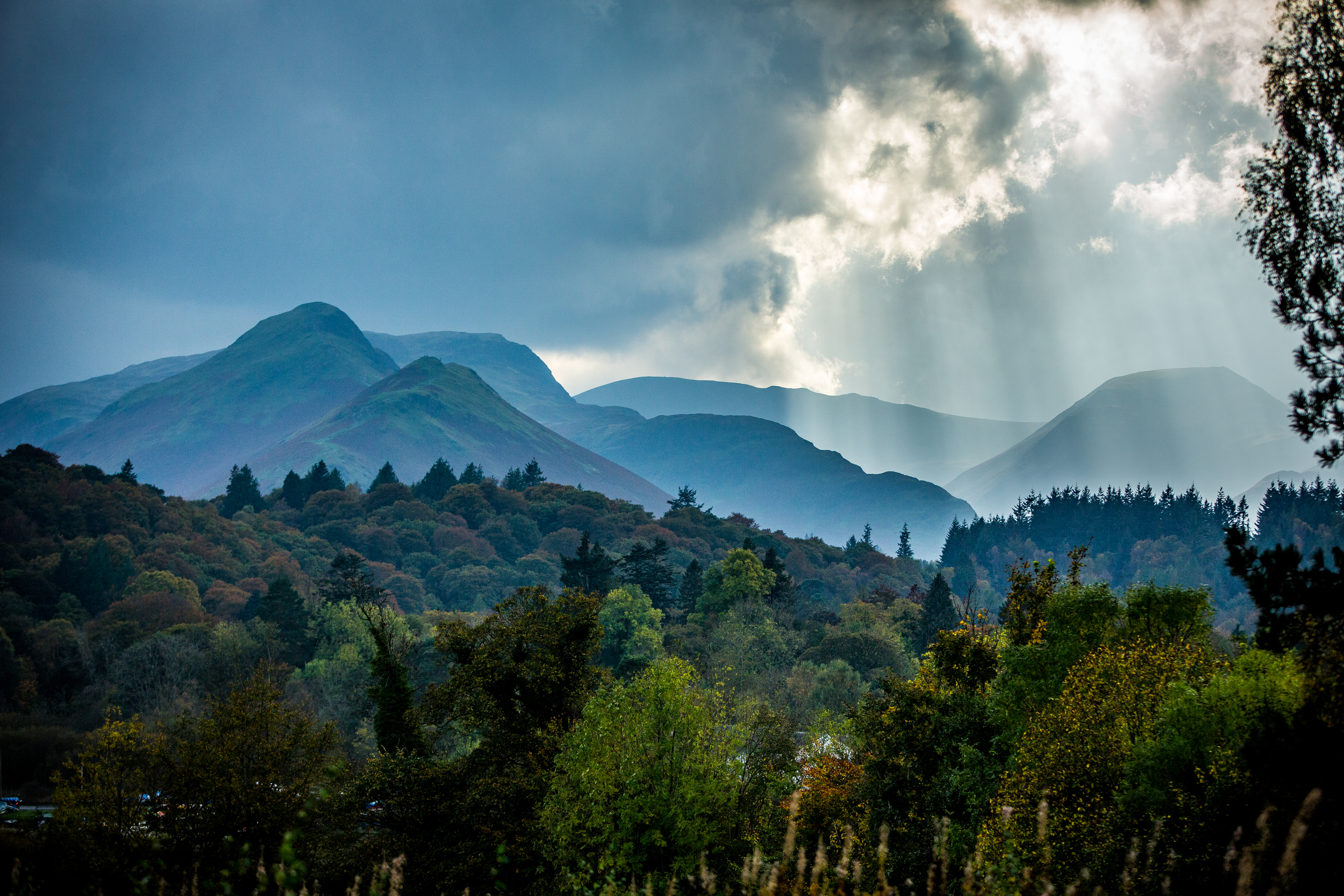 Sun rays breaking through and lighting up the Lake District mountains