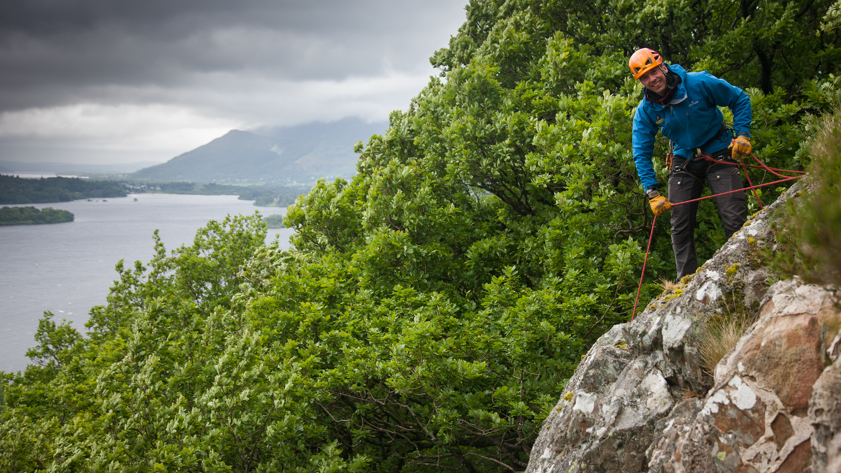 Neale managing an abseil session on a steep cliff above Derwent Water